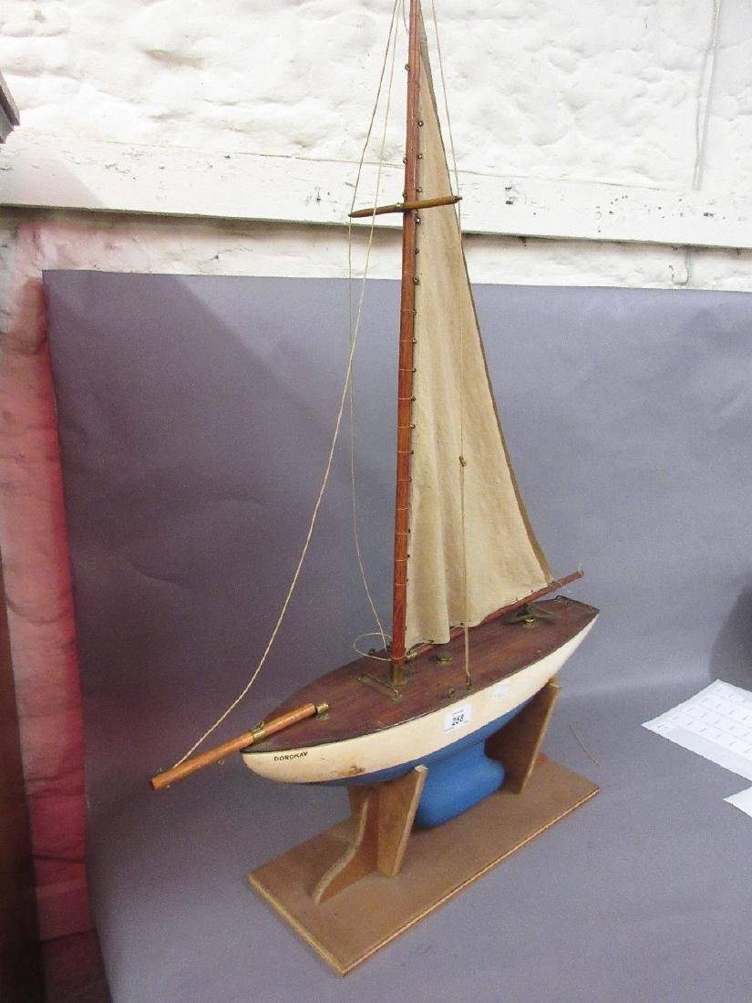 Small white and blue painted pond yacht with sail on