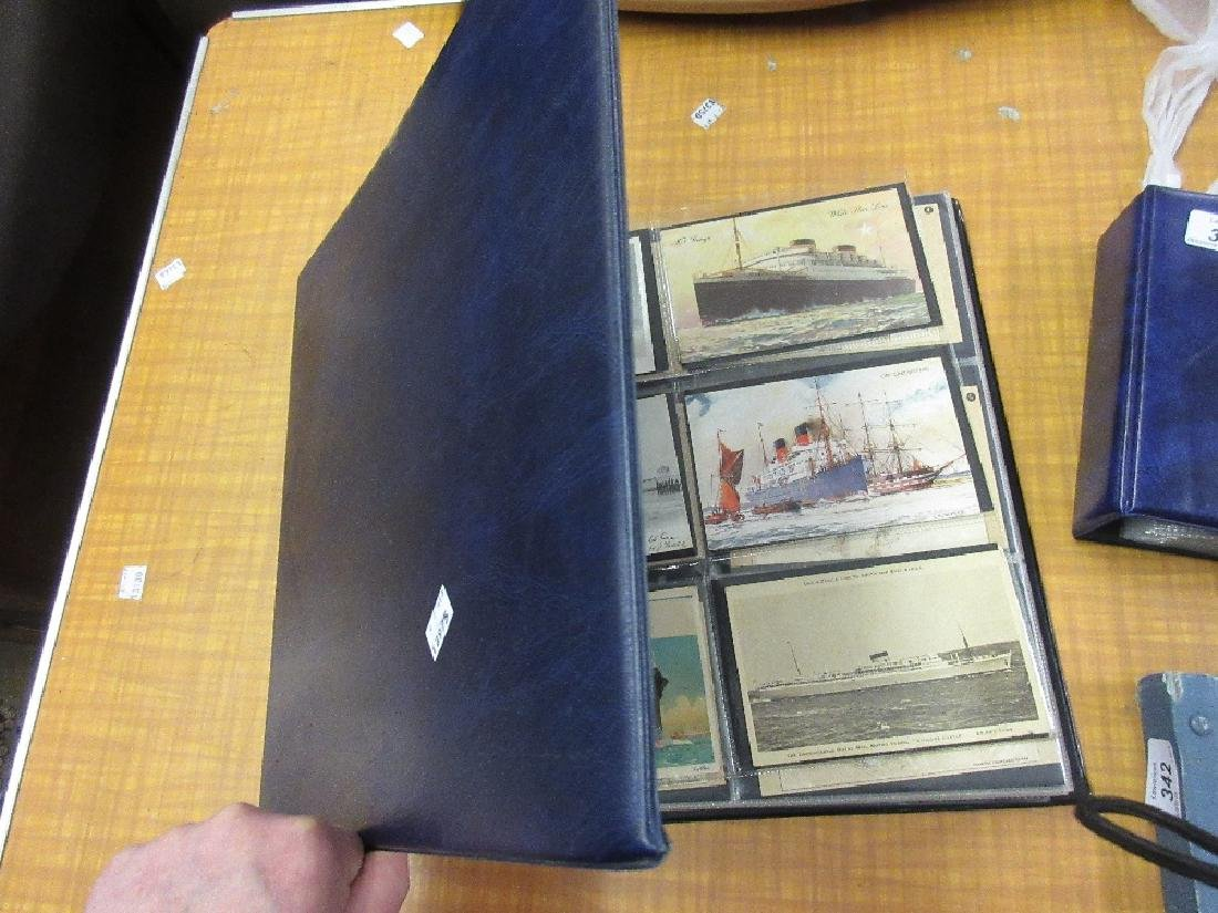 Blue album containing a collection of various postcards