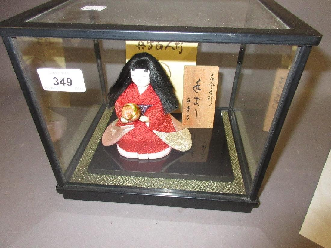 Japanese porcelain doll in a glazed display cabinet