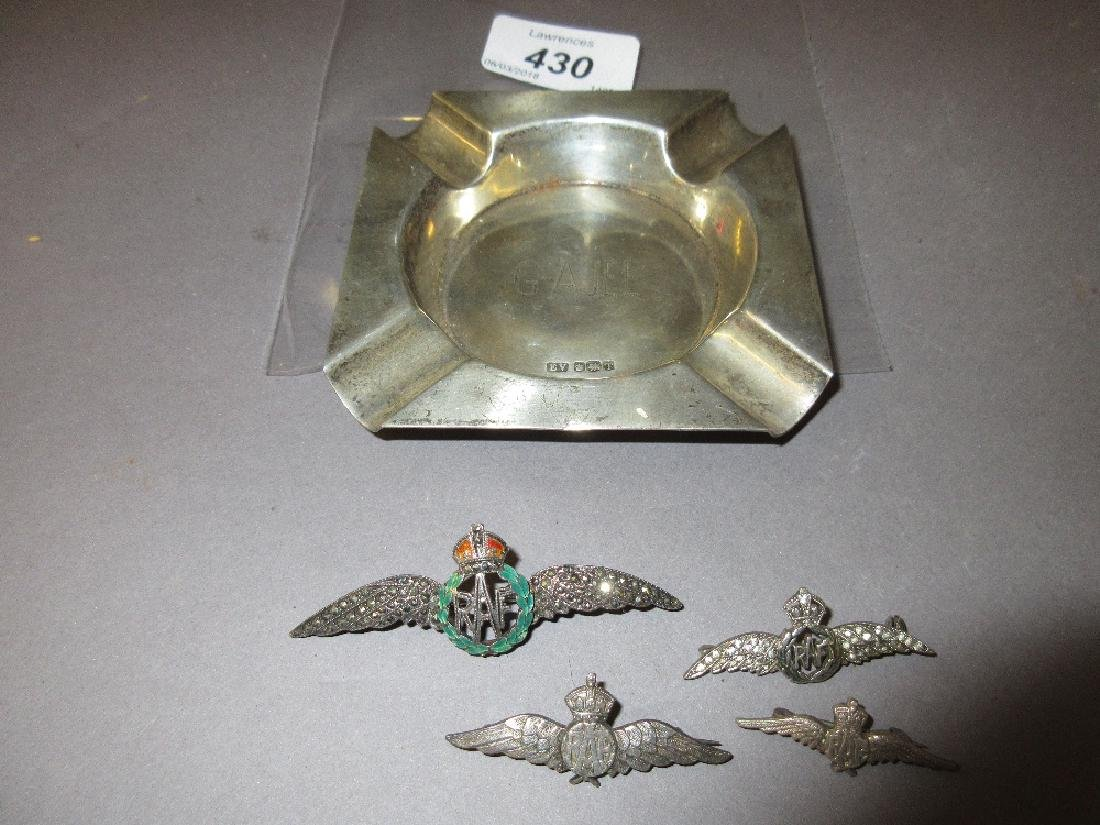 Four silver R.A.F. badges and a silver ashtray