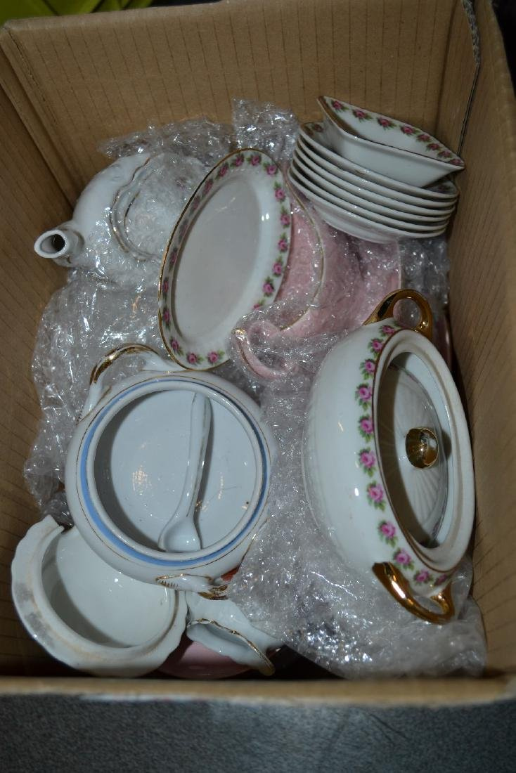 Box containing various dolls, porcelain plates,