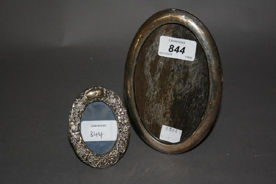Small oval silver mounted photograph frame and another