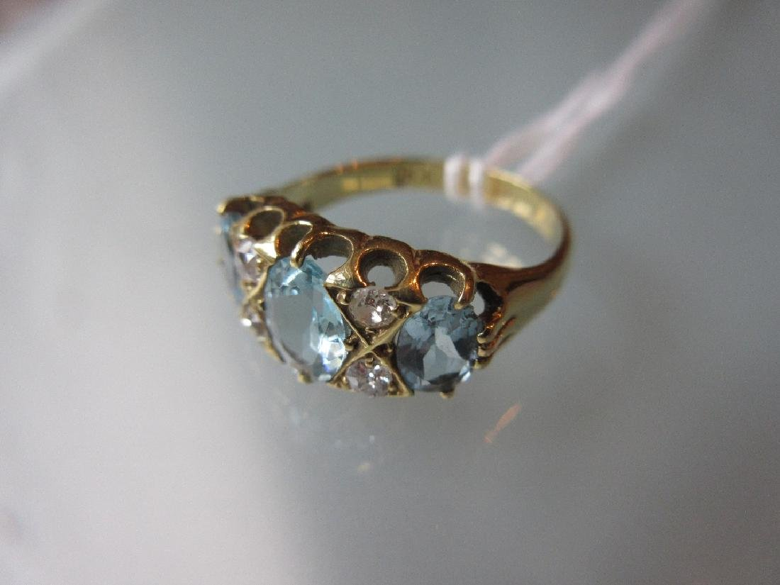 Yellow gold ring set three oval aquamarine and four