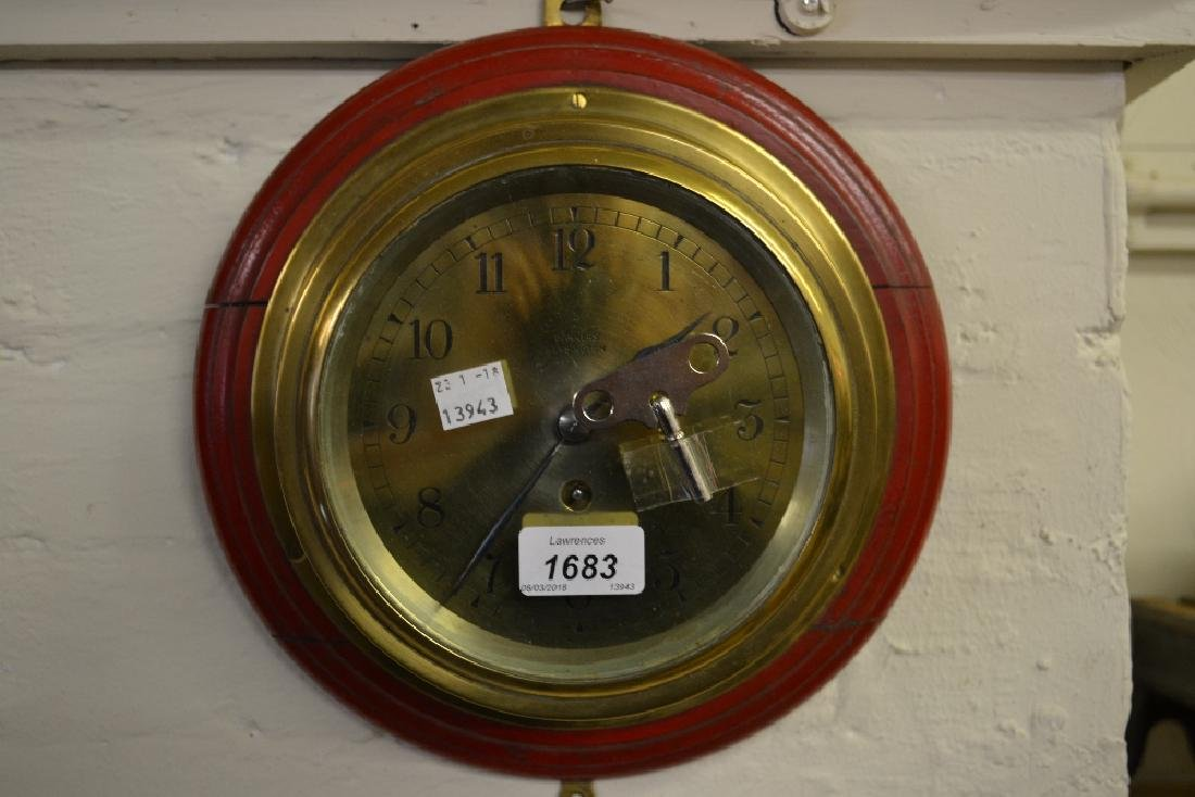 Circular brass cased ship's clock mounted on a wooden