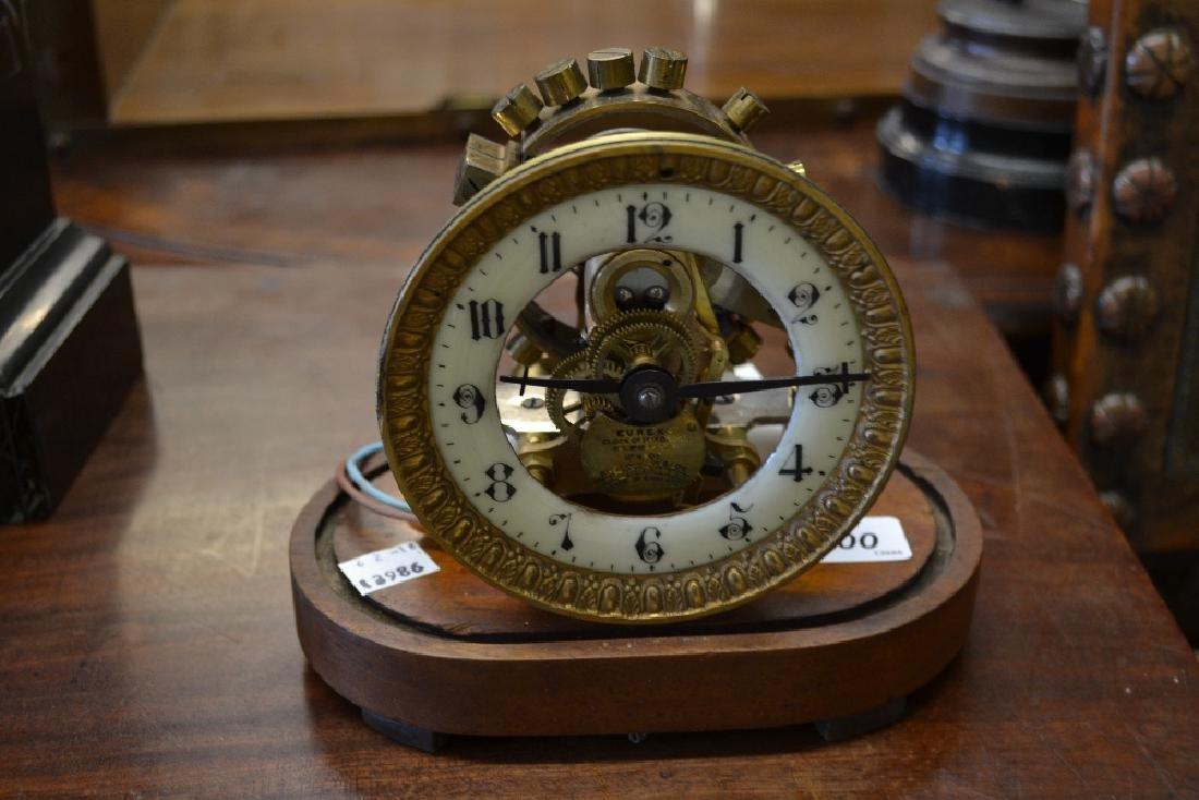 Eureka early battery clock on a mahogany plinth, the