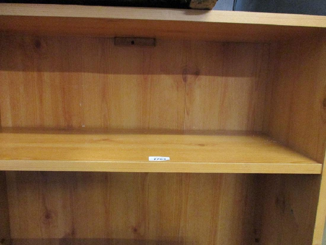 Three matching modern faux wood open bookcases together