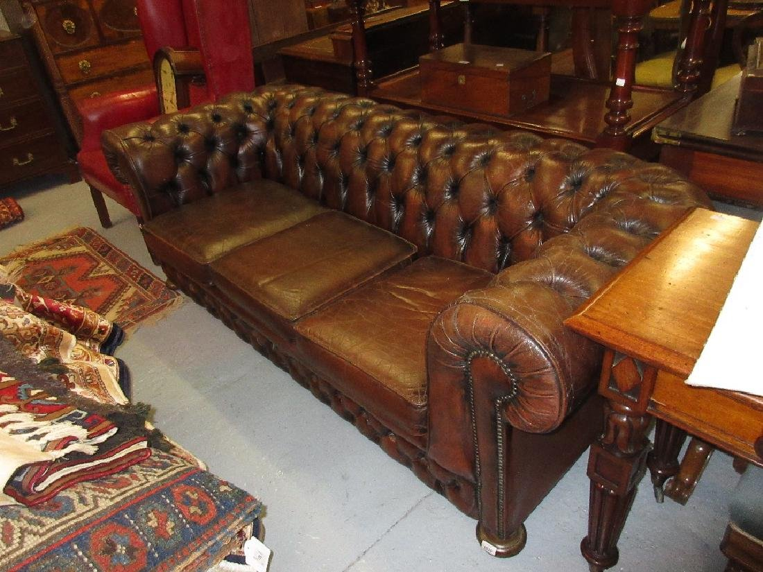 Brown leather Chesterfield three seat sofa having