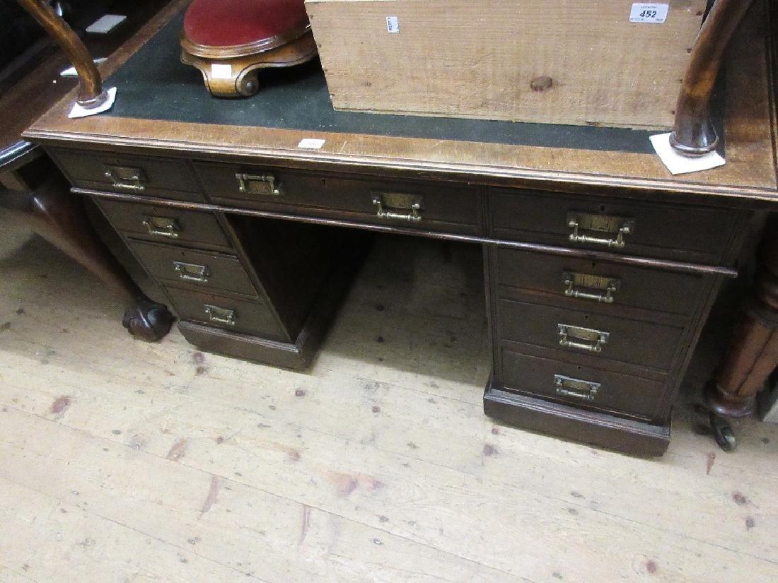 Late Victorian oak pedestal desk, the moulded top above
