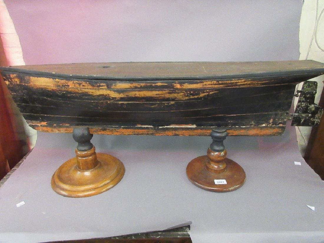Painted pine boat hull with metal rudder on associated