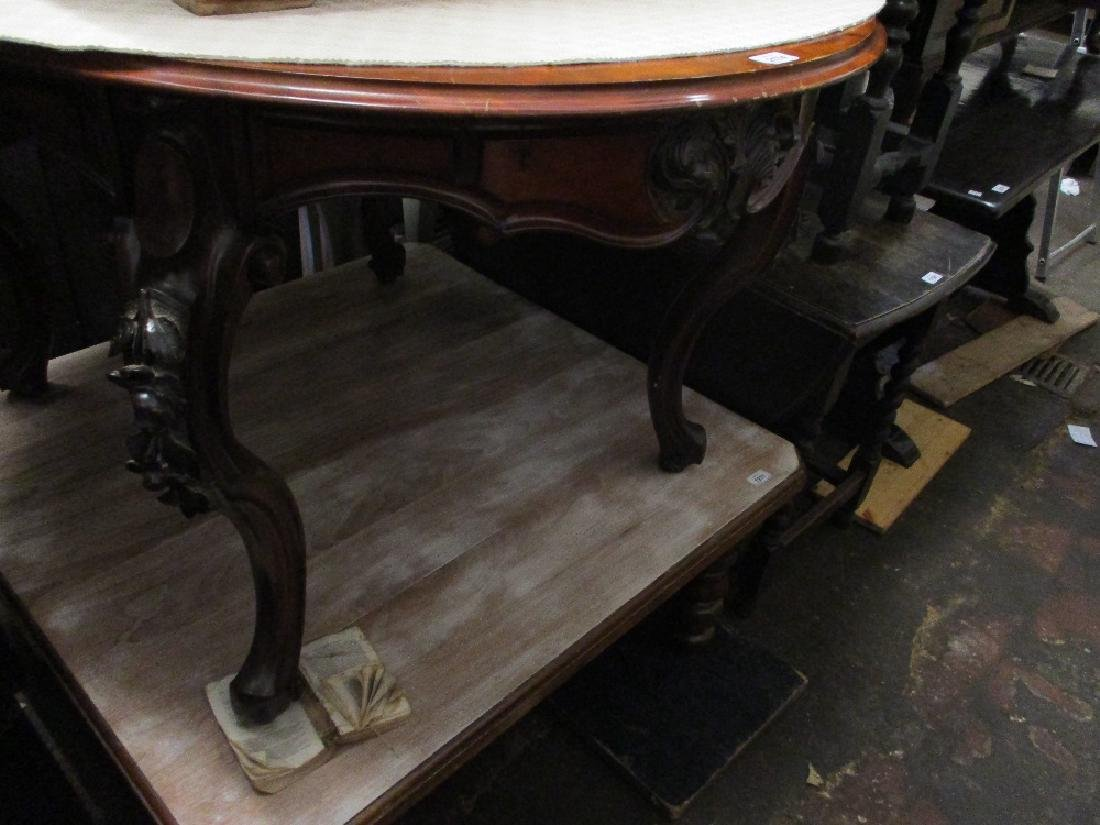 Continental oval mahogany centre table having carved