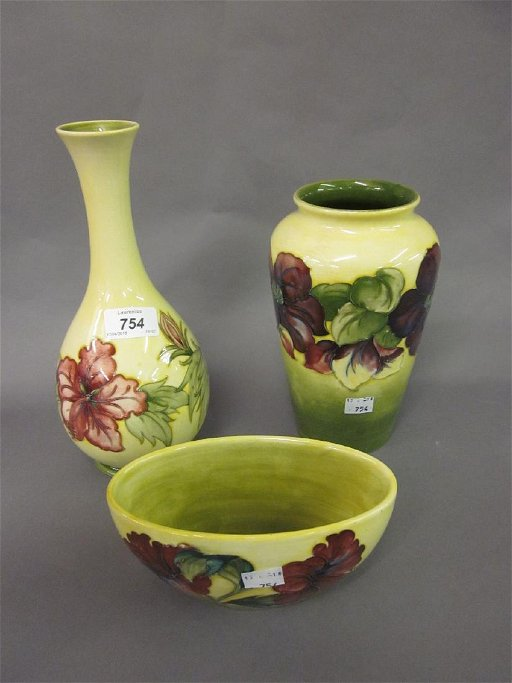 Two Moorcroft Hibiscus pattern vases on a green and