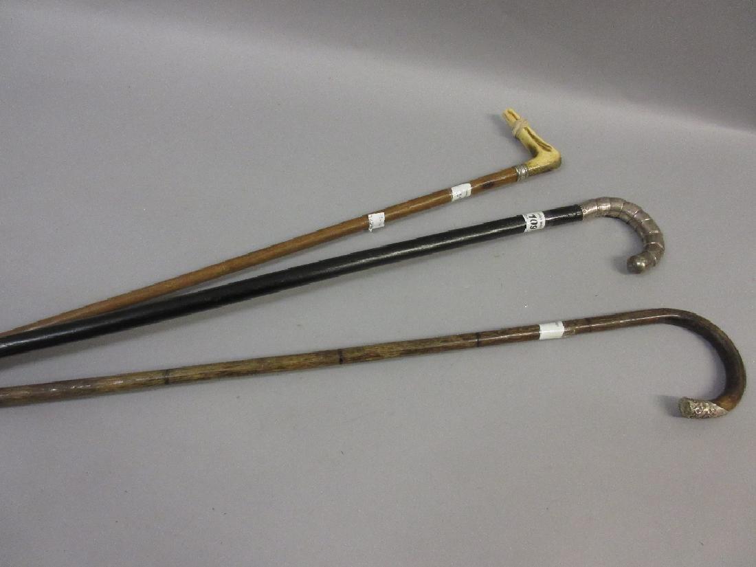 Three various white metal mounted walking sticks