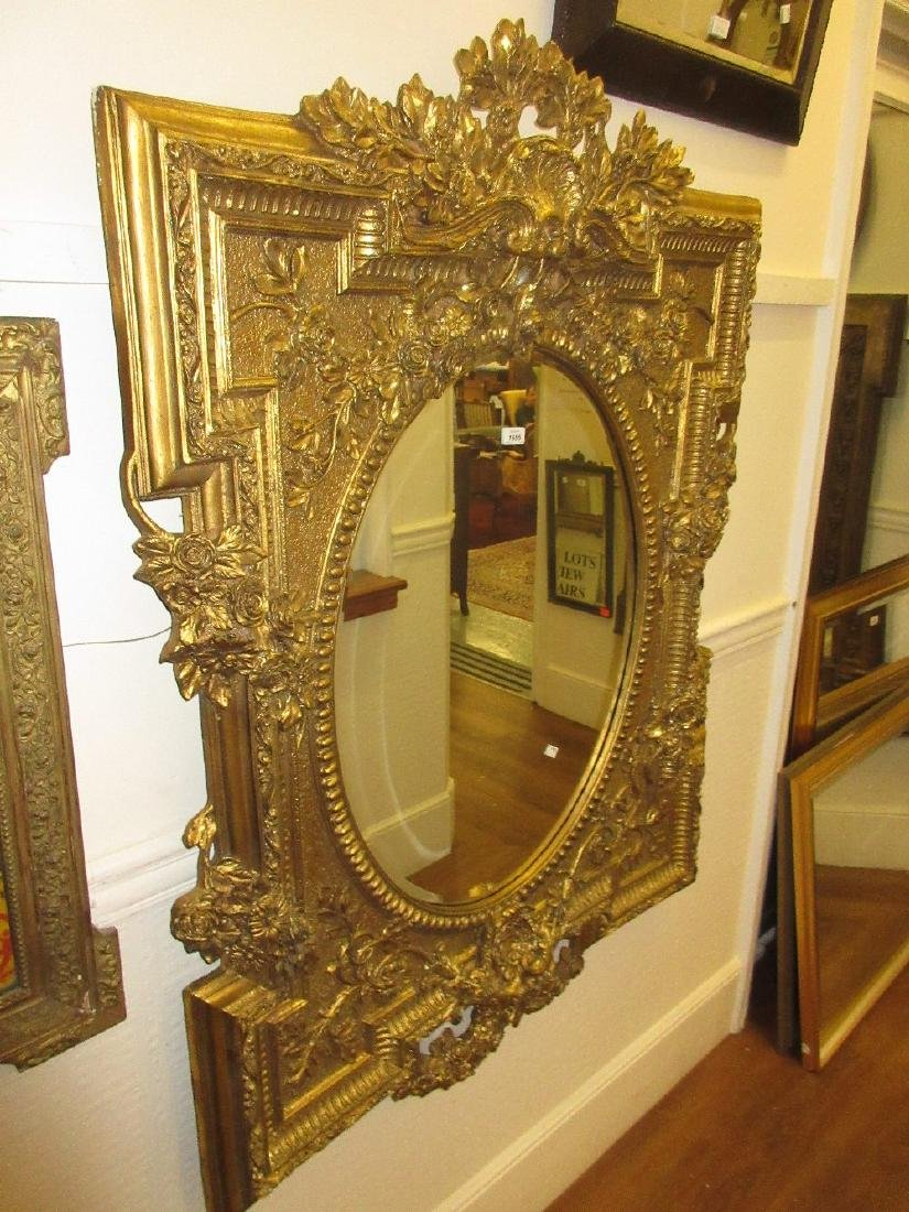 Large and ornate gilded composition wall mirror with