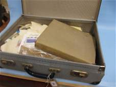 Small attache case containing a collection of loose