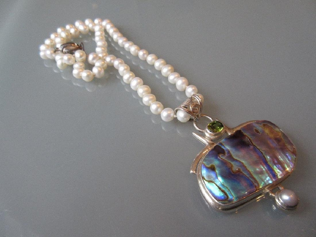 Abalone set silver pendant suspended from a cultured