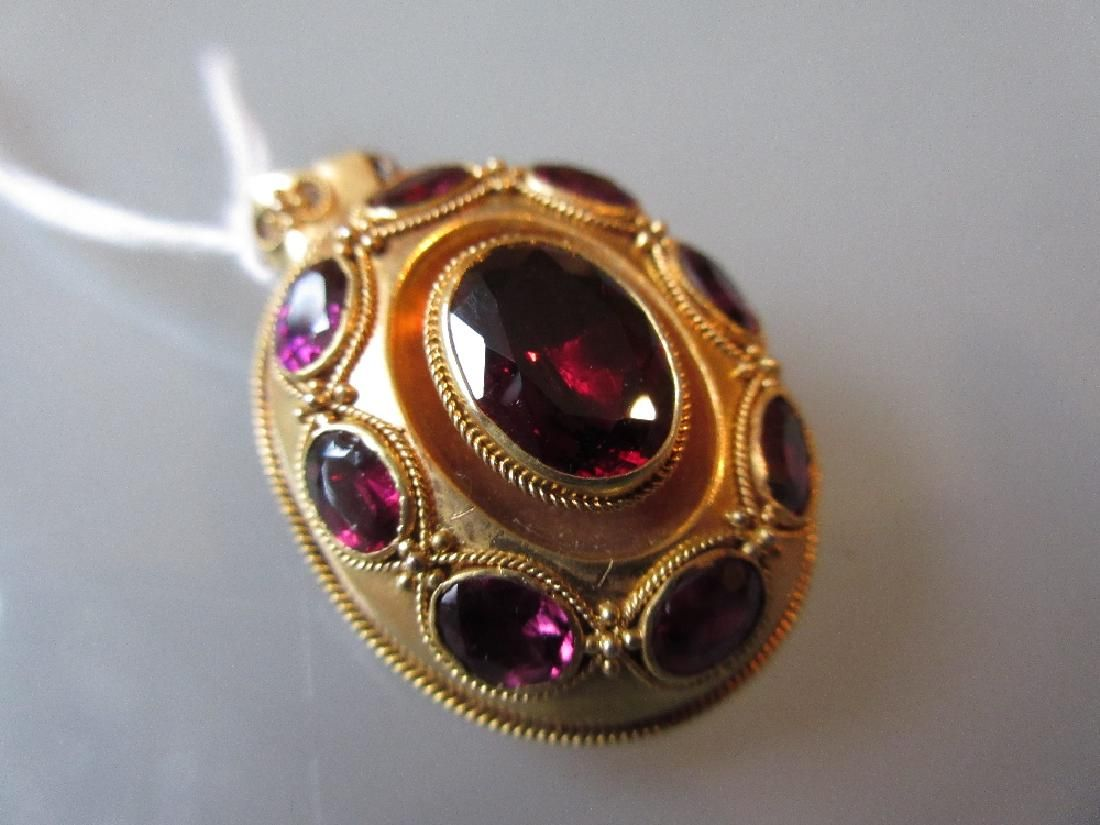 Victorian oval gold pendant locket set with a garnet