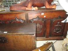 Antique oak coffer with a hinged top above four panel