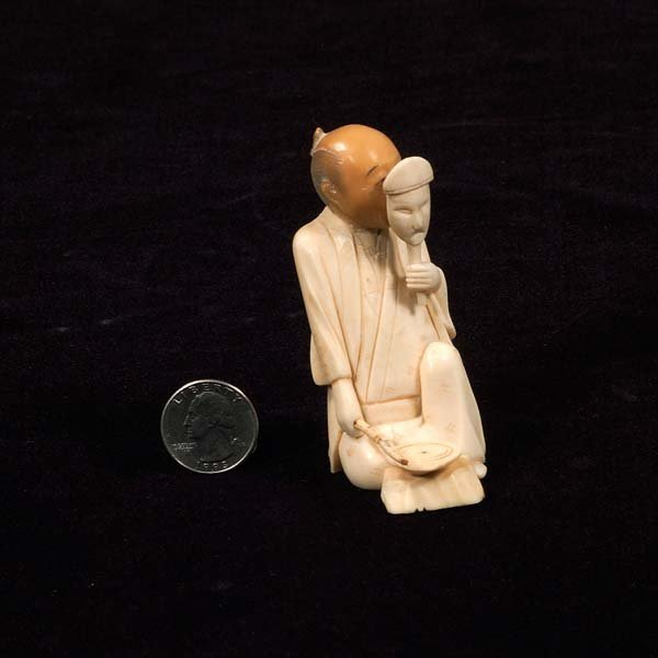12: Carved ivory figure of a seated man holding a mask,