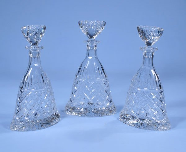1001: Group of three oval cut crystal decanters with cu
