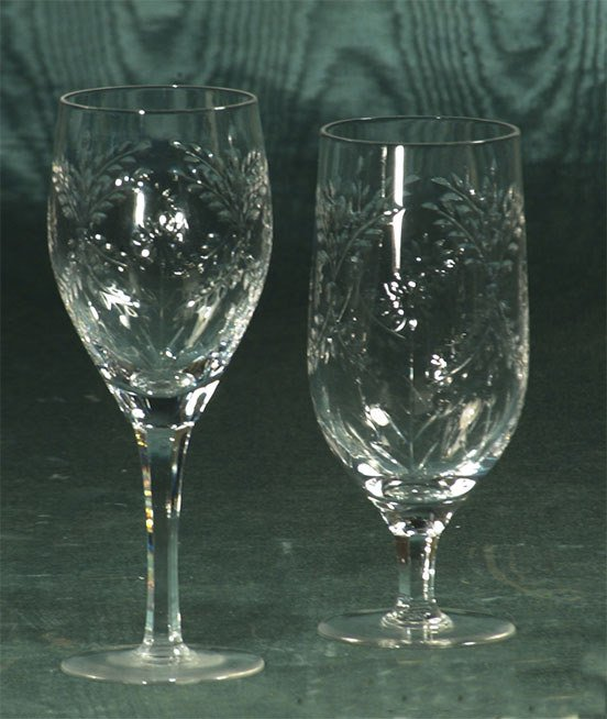 1002: Set of 12 etched crystal wine goblets, and 11 mat