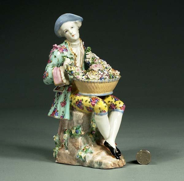 1016: French porcelain figure of a man with a basket of