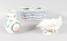 A FRENCH FAIENCE SAUCEBOAT, JUG AND CRUET STAND (3).
