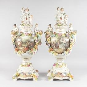 A LARGE PAIR OF DRESDEN STYLE TWO HANDLED URNS, COVERS