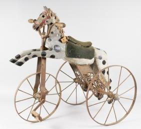 A CHILD'S EARLY CARVED AND PAINTED WOODEN TRICYCLE