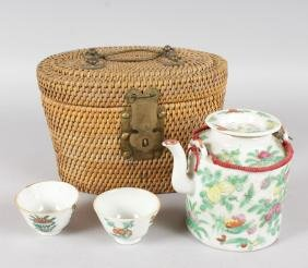 A CANTON PORCELAIN TEAPOT AND TWO TEA BOWLS in a wicker