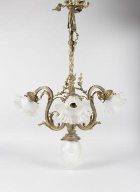 A BRASS CHANDELIER with four glass shades.