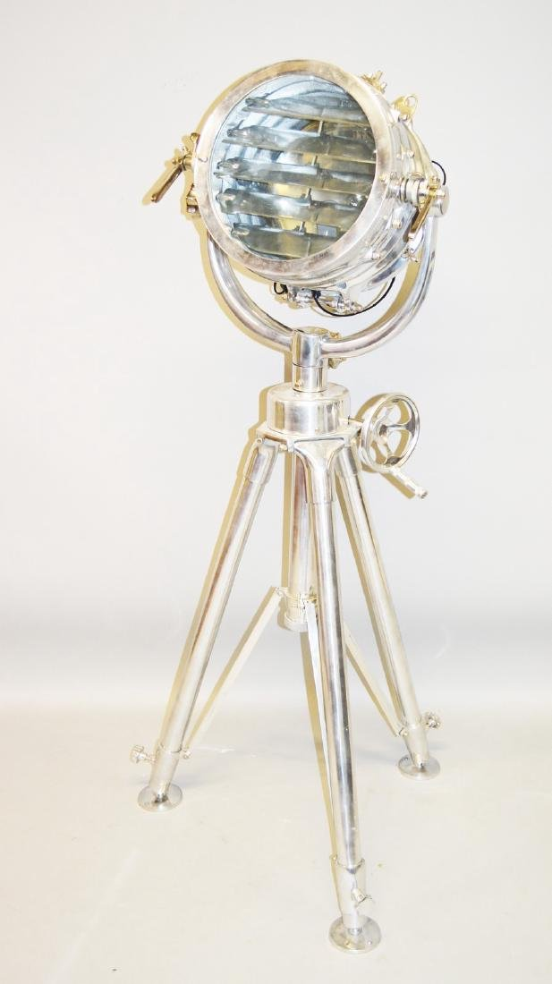 A LARGE CHROME FILM SEARCH LIGHT on a tripod stand.