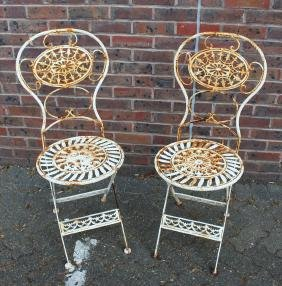 A PAIR OF WHITE PAINTED WROUGHT IRON CHAIRS.