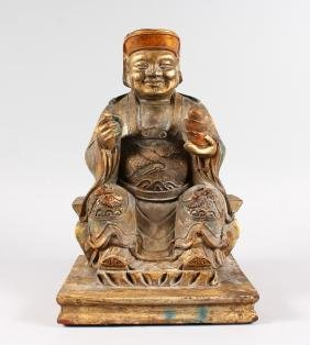 A CHINESE CARVED WOOD AND GILDED SEATED DEITY, seated