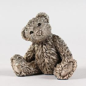 A SMALL SILVER TEDDY BEAR.