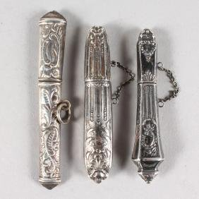 THREE SILVER NEEDLE CASES.