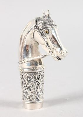 A WHITE METAL HORSES HEAD CANE HANDLE.