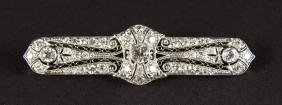 A GOLD ART DECO DIAMOND SET PLATINUM BAR BROOCH.