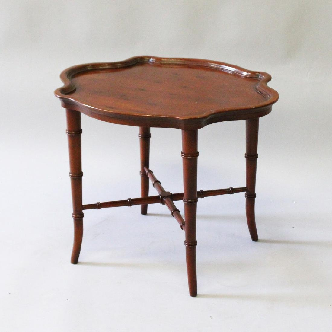 A SMALL MAHOGANY SHAPED TOP COFFEE TABLE on bamboo type