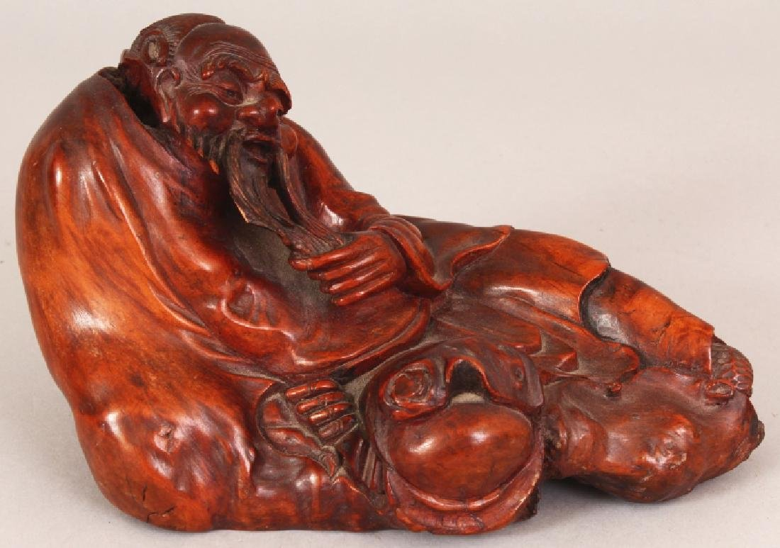 A 19TH CENTURY CARVED ROOTWOOD FIGURE OF A RECLINING