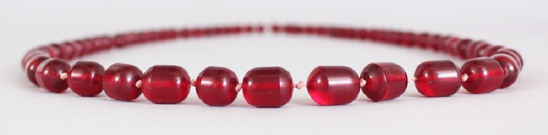 TWO RECONSTITUTED 'CHERRY AMBER' NECKLACES, weighing - 3