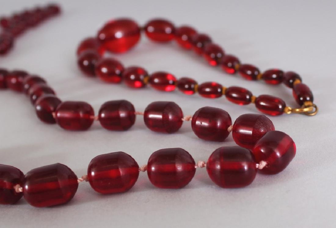 TWO RECONSTITUTED 'CHERRY AMBER' NECKLACES, weighing - 4