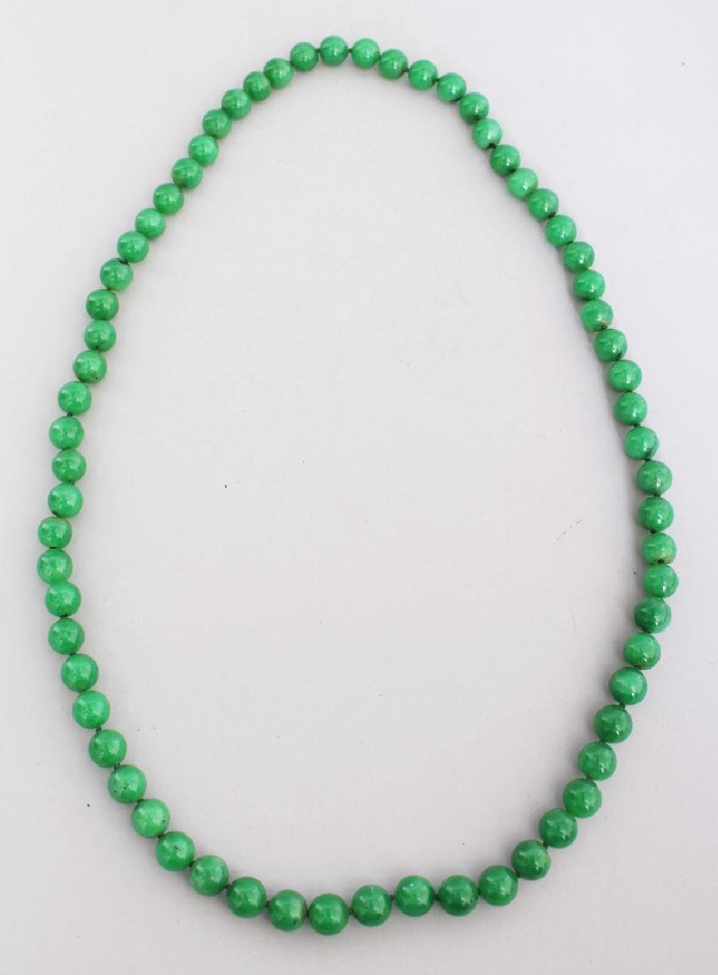 A STRING OF CHINESE APPLE GREEN JADE BEADS, each bead