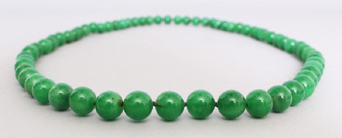 A STRING OF CHINESE APPLE GREEN JADE BEADS, each bead - 2
