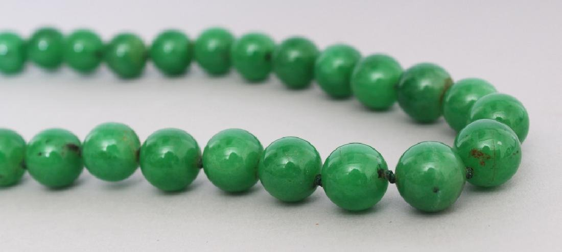 A STRING OF CHINESE APPLE GREEN JADE BEADS, each bead - 3