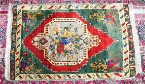 AN OLD SMALL PERSIAN RUG with central floral motif.