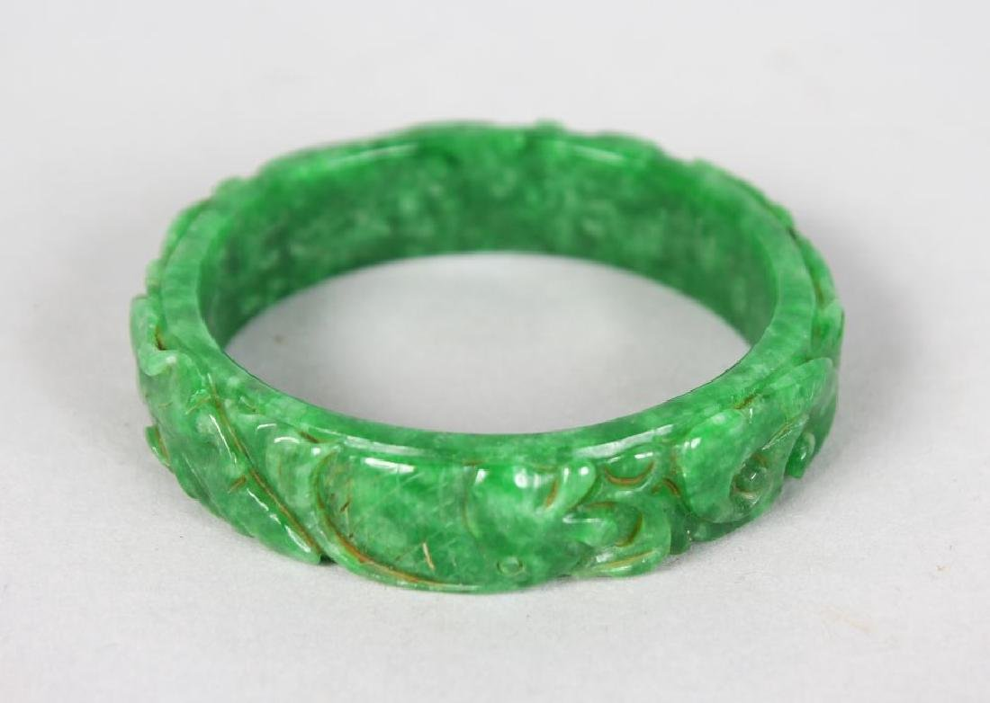 A CHINESE CARVED APPLE GREEN JADE BANGLE.