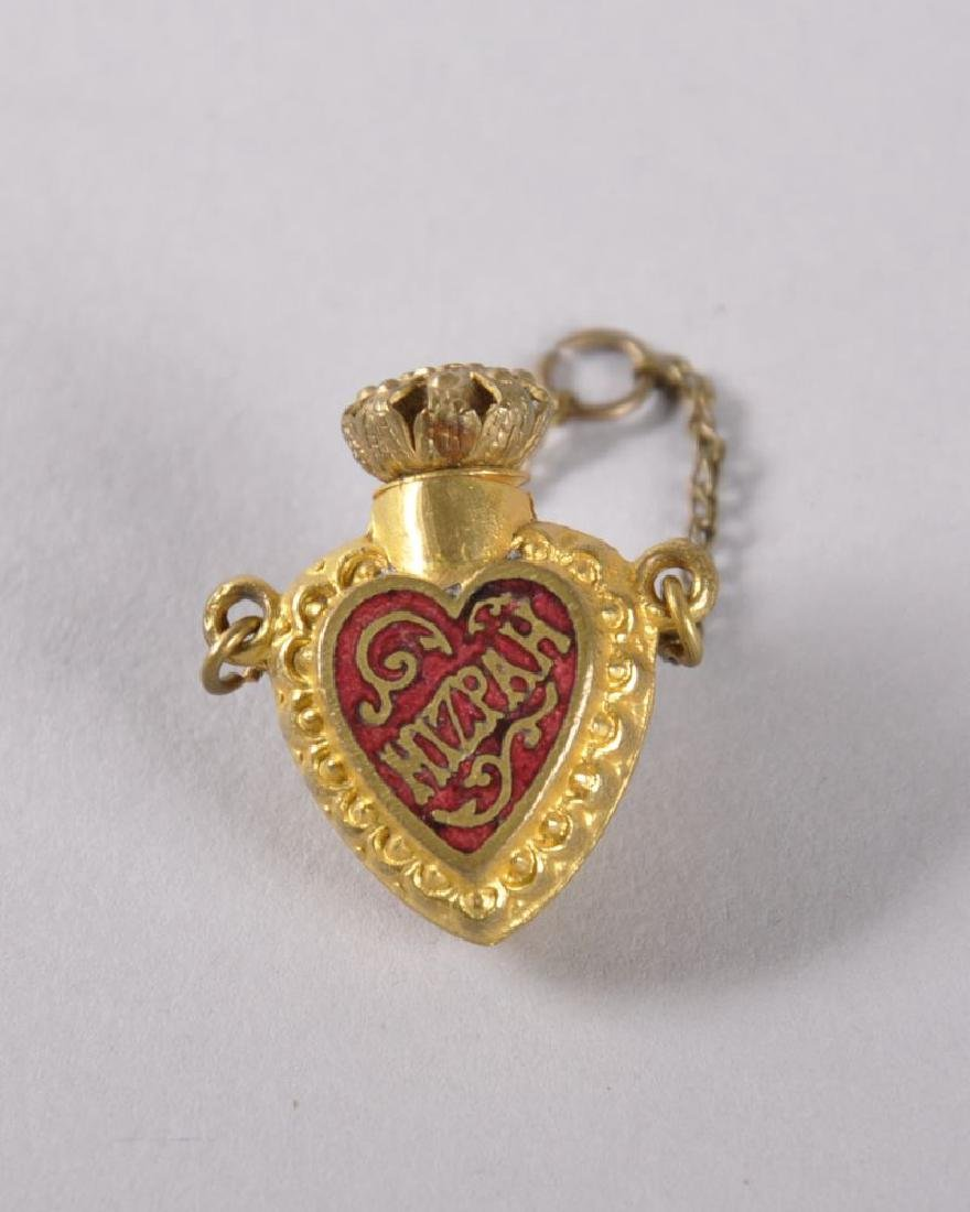 A MINIATURE HEART SHAPED GILT PERFUME BOTTLE on a
