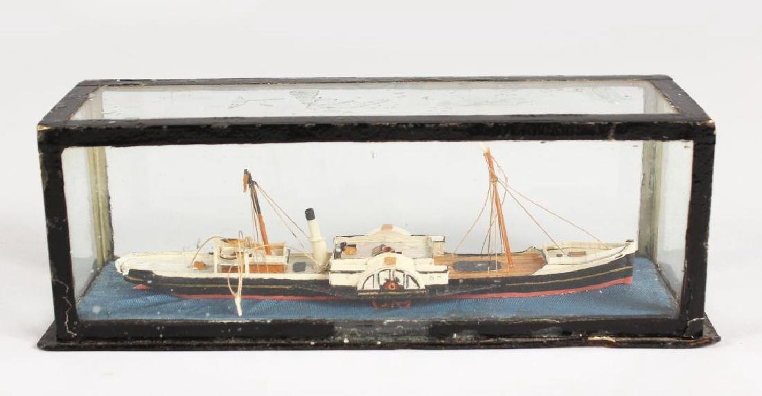 A MINIATURE BOAT in a glass case.  7ins long.
