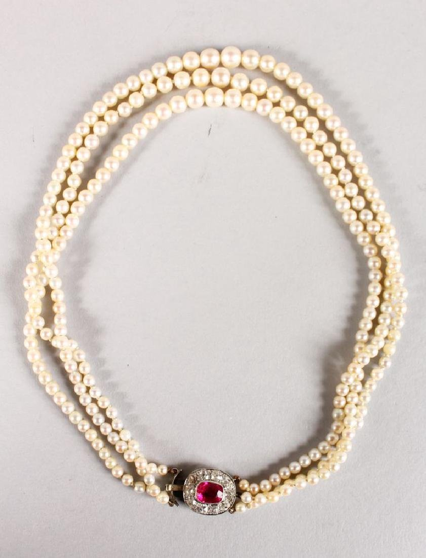 A VERY GOOD TRIPLE ROW PEARL NECKLACE with ruby and