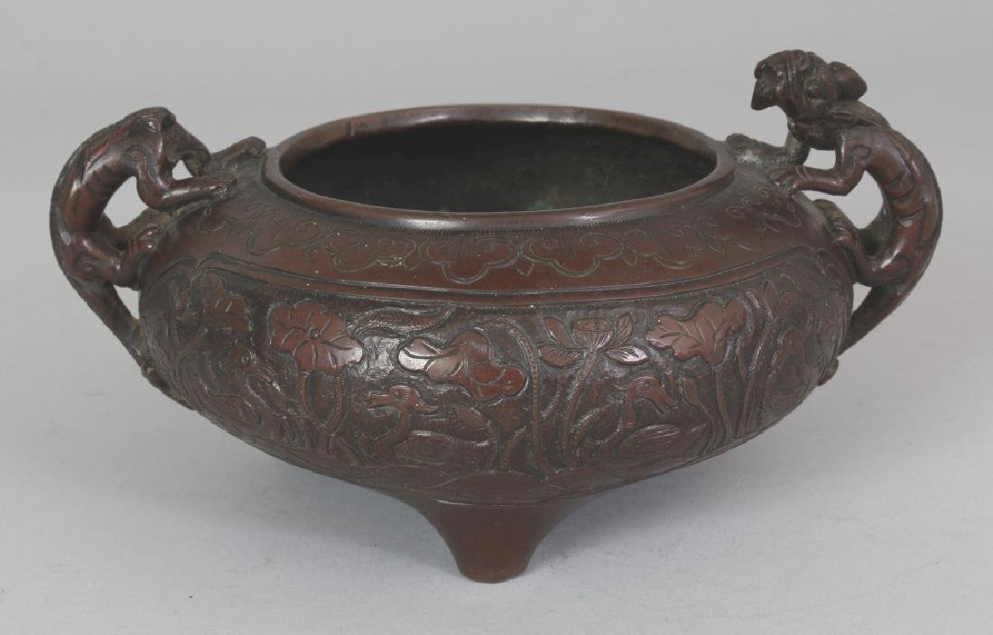 A CHINESE BRONZE TRIPOD CENSER, the base cast with a